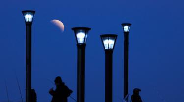 Sejumlah pria berdiri di bawah lampu jalan ketika fenomena gerhana bulan sebagian (parsial) di Buenos Aires, Argentina, Selasa (16/7/2019). Gerhana bulan parsial ini bisa diamati dari Amerika Selatan, Eropa, Afrika, Asia dan Australia. (AP Photo/Natacha Pisarenko)