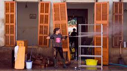 Seorang wanita membersihkan rumahnya yang terkena banjir bandang di Sant Llorenc, Mallorca, Spanyol (11/10). Banjir bandang tersebut telah menewaskan setidaknya 10 orang. (AP Photo/Francisco Ubilla)
