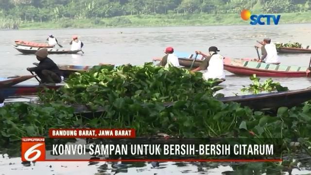 Ratusan warga Bandung konvoi menggunakan sampan untuk membersihkan sampah dan eceng gondok di Sungai Citarum, Bandung Barat.