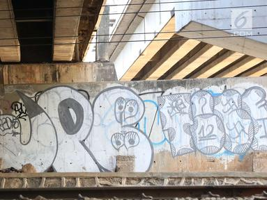Pencari barang bekas melintasi kolong Flyover Kuningan, Jakarta, Selasa (25/9). Coretan terlihat memenuhi dinding kolong Flyover Kuningan. (Liputan6.com/Immanuel Antonius)