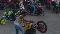 Warga menyaksikan atraksi para freestyle dengan motor di kawasan Kanal Banjir Timur, Jakarta, Selasa (29/5). Sekelompok pemuda di kawasan itu memanfaatkan waktu menunggu berbuka dengan melakukan atraksi freestyle yang mendebarkan (Merdeka.com/Imam Buhori)