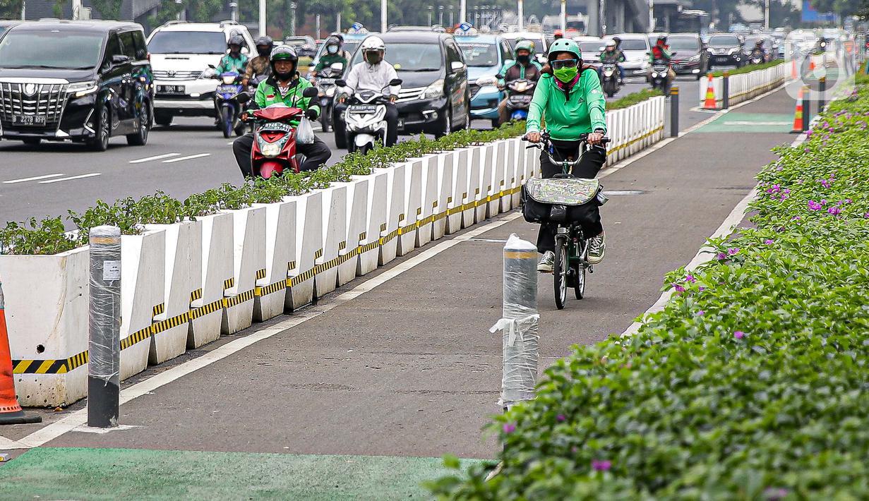 Pesepeda melintasi jalur khusus sepeda yang diberikan pembatas jalur permanen di kawasan Sudirman, Jakarta, Kamis (17/6/2021). Kapolri Jenderal Listyo Sigit Prabowo akan membongkar jalur sepeda di Jalan Sudirman-Thamrin dan mempelajari jalur khusus sepeda di negara lain. (Liputan6.com/Faizal Fanani)