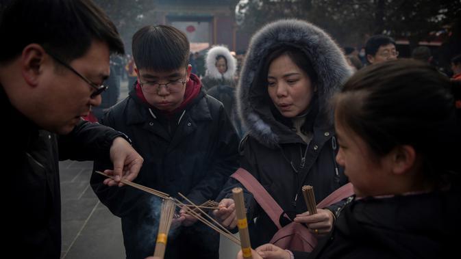 Keluarga membakar dupa untuk berdoa keberuntungan pada hari kelima Tahun Baru Imlek di Yonghegong, atau Kuil Lama di Beijing (9/2). Warga China merayakan Tahun Babi tersebut dengan doa, pesta keluarga, dan belanja. (AFP Photo/Nicolas Asfouri)#source%3Dgooglier%2Ecom#https%3A%2F%2Fgooglier%2Ecom%2Fpage%2F%2F10000