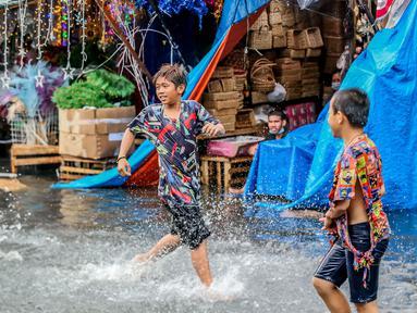 Anak-anak bermain di tengah banjir usai hujan deras yang tiba-tiba mengguyur di sebuah pasar dekorasi Natal di Manila, Filipina (9/12/2020). (Xinhua/Rouelle Umali)