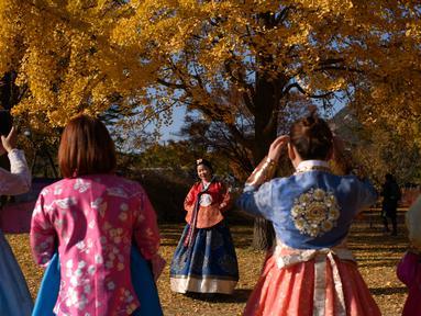 Pengunjung yang mengenakan pakaian tradisional hanbok berpose untuk foto di bawah pohon ginkgo di istana Gyeongbokgung di Seoul (31/10). Pohon Ginkgo yang berasal dari Tiongkok ini dikenal sebagai pohon rambut gadis. (AFP Photo/Ed Jones)