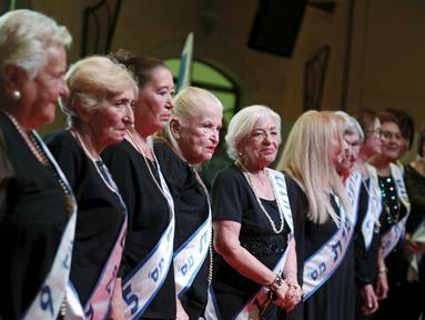 Para peserta berdiri di atas panggung saat mengikuti kontes kecantikan Miss Holocaust Survivor di Israel, Selasa (24/11). 13 wanita lansia mengikuti kontes kecantikan tahun ketiga yang diperuntukkan bagi korban selamat genosida Nazi. (REUTERS/Amir Cohen)