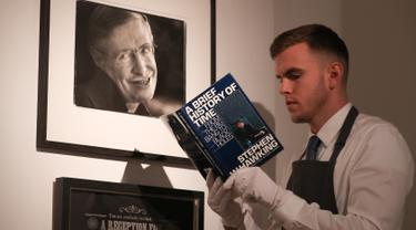 "Asisten galeri berpose dengan salinan buku ""A History of Time"" yang ditandatangani dengan cap jempol oleh fisikawan Stephen Hawking selama sesi pemotretan untuk acara pelelangan di Balai Lelang Christie, London, Selasa (30/10). (Daniel LEAL-OLIVAS/AFP)"