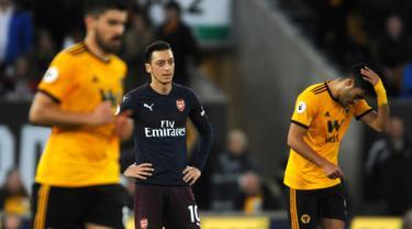 Megaintang Arsenal, Mesut Ozil bereaksi setelah pemain Wolverhampton Wanderers, Matt Doherty mencetak gol pada laga lanjutan Liga Inggris 2018-2019 di Stadion Molineux, Rabu (24/4). Arsenal harus tumbang dengan skor 1-3 kala bertandang ke markas Wolverhampton Wanderers. (AP Photo/Rui Vieira)
