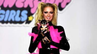 Paris Hilton membawa anjing saat tampil dalam Christian Cowan x The Powerpuff Girls Fashion Show, Los Angeles, AS, Jumat (8/3). Anjing tersebut merupakan peliharaannya yang bernama Diamond Baby. (Frazer Harrison/Getty Images North America/AFP)