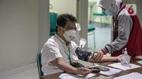 Tenaga kesehatan menjalani pemeriksaan sebelum disuntik vaksin COVID-19 produksi Sinovac oleh vaksinator saat kegiatan vaksinasi di RSCM di Jakarta, Senin (8/2/2021). Kementerian Kesehatan secara resmi memulai vaksinasi tenaga kesehatan di atas 60 tahun pada hari ini. (Liputan6.com/Faizal Fanani)
