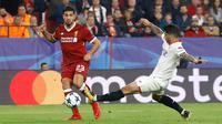 Pemain Sevilla, Ever Banega dan pemain Liverpool, Emre Can berebut bola pada laga kelima Grup E Liga Champions di Stadion Ramon Sanchez Pizjuan, Rabu (22/11). Sempat unggul tiga gol, Liverpool kemudian justru diimbangi Sevilla 3-3. (AP/Miguel Morenatti)