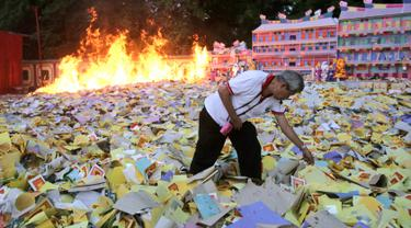Seorang pria etnis Tionghoa membakar uang arwah saat festival Hungry Ghost atau Hantu Kelaparan di Medan, Sumatera Utara (5/9). Di Indonesia festival ini lebih dikenal dengan perayaan Zhong Yuan. (AP Photo/Binsar Bakkara)