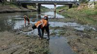 Petugas UPK Badan Air Dinas Lingkungan Hidup Provinsi DKI Jakarta membersihkan rerumputan dan sampah di dasar aliran Kanal Banjir Timur, Jakarta, Rabu (7/8/2019). Kemarau berkepanjangan mengakibatkan debit air Kanal Banjir Timur menyusut hingga dasar aliran terlihat. (merdeka.com/Iqbal Nugroho)