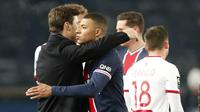 Pelatih Paris Saint-Germain (PSG), Mauricio Pochettino, memeluk Kylian Mbappe usai pertandingan melawan Brest pada laga Liga Prancis di Stadion Parc des Princes, Sabtu (9/1/2021). PSG menang dengan skor 3-0. (AP Photo/Francois Mori)