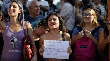 Seorang wanita memegang tulisan bernada protes saat unjuk rasa di Ibu Kota Argentina, Buenos Aires, Selasa (7/1). Aksi itu sebagai bentuk protes atas kekerasan yang dilakukan aparat kepolisian terhadap perempuan tanpa bra. (AP Photo/Natacha Pisarenko)