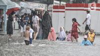 Anak-anak saat bermain di tengah banjir yang merendam Jalan Abdullah Syafei, Tebet, Jakarta, Kamis (18/2/2021). Menurut warga setempat, banjir ini merupakan yang pertama kali terjadi yang diduga disebabkan adanya proyek revitalisasi kolong flyover. (merdeka.com/Iqbal S Nugroho)