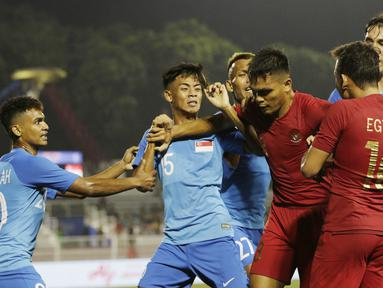Pemain Timnas Indonesia U-22, Rachmad Irianto, melerai Egy Maulana, saat bersitegang dengan pemain Singapura U-22 pada laga SEA Games 2019 di Stadion Rizal Memorial, Manila, Kamis (28/11). Indonesia menang 2-0 atas Singapura. (Bola.com/M Iqbal Ichsan)