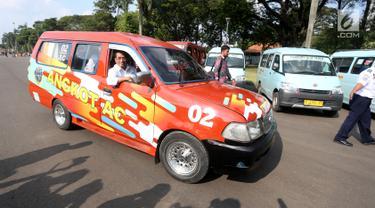 Menhub Budi Karya Sumadi mengemudikan angkot sambil saat meluncurkan program Angkutan Kota ber-AC di Monas, Jakarta, Sabtu (1/7). Kemenhub  meluncurkan angkot ber-AC di kawasan DKI Jakarta, Kota Bekasi, Bogor dan Tangerang (Liputan6.com)
