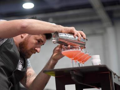 Bartender Mariano Gil menyajikan minuman saat berkompetisi dalam Shake It Up Flair Competition pada hari kedua dari Nightclub & Bar Convention and Trade Show tahunan ke-34 di Las Vegas, Nevada (26/3). (AFP Photo/Ethan Miller)