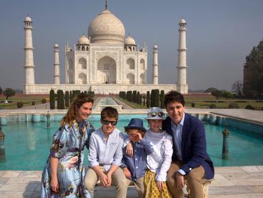 PM Kanada Justin Trudeau bersama sang istri, Sophie Gregoire Trudeau serta tiga anaknya berpose di depan Taj Mahal di sela-sela kunjungan ke India, Minggu (18/2). Ini adalah kunjungan pertama Tredeau ke India sejak menjabat pada 2015. (AP/Manish Swarup)