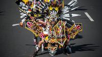 Aksi seorang peserta mengenakan kostum adat Indonesia saat berpartisipasi dalam parade Jember Fashion Carnaval 2017 di pulau Jawa timur (13/8). Sekitar 2000 peserta mengelilingi rute 3,6 kilometer di sekitar kota. (AFP Photo/Juni Kriswanto)