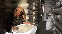 Pekerja membersihkan beras di Pasar Induk Beras Cipinang, Jakarta, Senin (15/1). Wagub Sandiaga Uno mengatakan Pemprov DKI akan selalu membeli beras Sulawesi dan Banten karena lebih memprioritaskan beras dari petani. (Liputan6.com/Immanuel Antonius)
