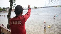 Penjaga pantai berjaga di Beach Pool Ancol, Jakarta, Selasa (25/12). Pasangnya air laut dan cuaca buruk mengakibatkan pantai Ancol sepi pengunjung saat libur Natal 2018. (Liputan6.com/Faizal Fanani)
