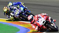 Aksi pebalap Yamaha, Valentino Rossi (kiri) saat berusaha menyalip pebalap lainnya di lintas balap Moto GP di grand Prix Valencia di Circuit Ricardo Tormo, Valencia, Minggu (8/11). (AFP PHOTO / JAVIER Soriano)