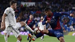 Gelandang Real Madrid, Marcos Llorente, berebut bola dengan striker Huesca, Cucho Hernandez, pada laga La Liga Spanyol di Stadion Santiago Bernabeu, Madrid, Minggu (31/3). Madrid menang 3-2 atas Huesca. (AFP/Javier Soriano)