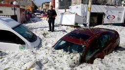 Seorang polisi berdiri di dekat kendaraan yang tertimbun salju di jalanan di wilayah timur Guadalajara, negara bagian Jalisco, Meksiko (30/6/2019). Salju yang turun di kota itu cukup tebal, bahkan di beberapa tempat mencapai 1,5 meter. (AFP Photo/Ulises Ruiz)