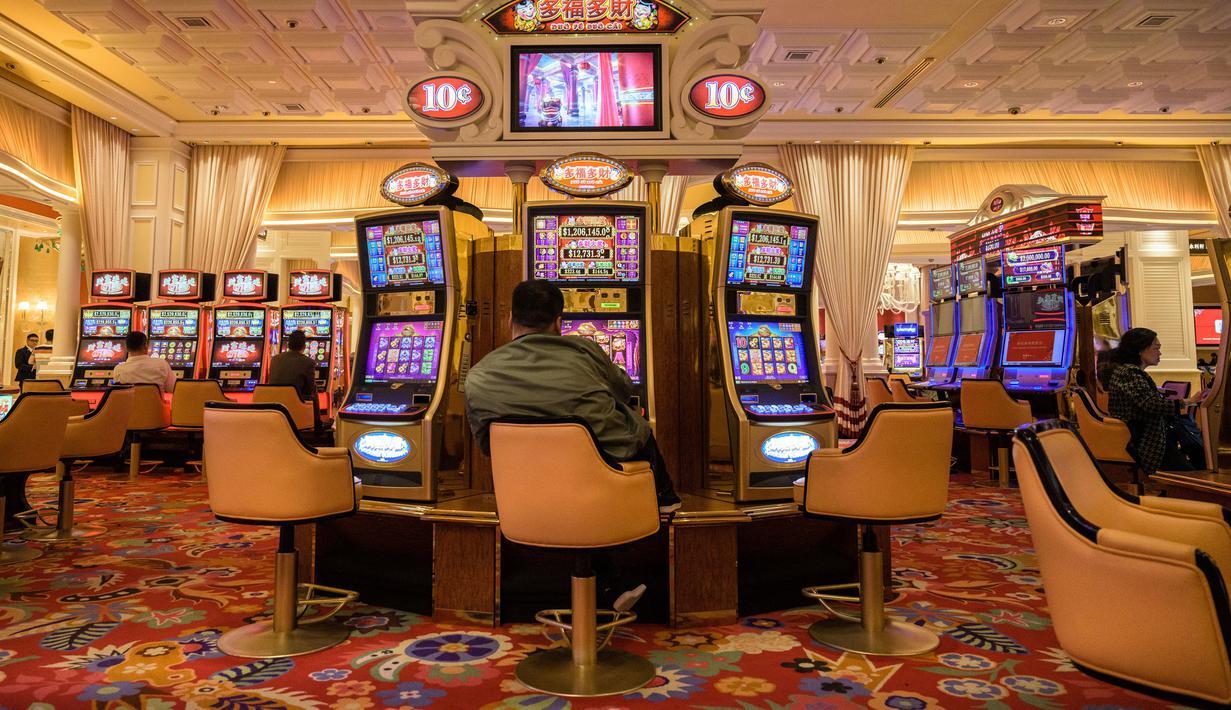 Pengunjung bermain mesin slot di sebuah resor di Macau, 5 Maret 2019. Macau merupakan kota judi terbesar di Asia. (Anthony Wallace/AFP)