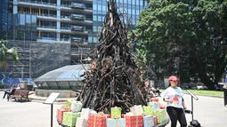 "Seorang wanita berpose di depan instalasi yang dijuluki 'Pohon Natal yang Terbakar' di Sydney (18/12/2019). Warga Australia di pantai timur bersiap menghadapi ""ancaman baru"" ketika gelombang panas disertai dengan angin yang bergolak menurunkan lebih dari 100 kebakaran hutan di kawasan itu. (AFP/Pete"