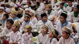 Anak-anak menunggu waktu berbuka puasa pada acara buka puasa bersama 1.100 anak yatim di Jakarta, Senin (20/5). Kegiatan yang bertemakan ' Ramadhan Cahya Keberkahan'  Agung Podomoro Land melalui Yayasan Agung Podomoro Land menggelar buka puasa bersama 1.100 anak yatim. (Liputan6.com/Faizal Fanani)