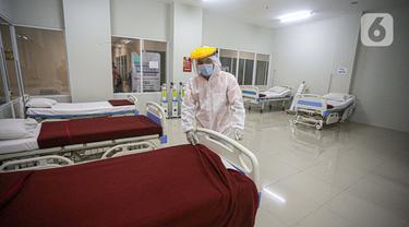 Petugas mengenakan hazmat saat menyiapkan tempat tidur di Tower 8 Wisma Atlet Pademangan, Jakarta, Selasa (15/6/2021). Koordinator Lapangan RSDC Wisma Atlet Letkol Marinir M. Arifin mengatakan soal alternatif Tower 8 Wisma Atlet Pademangan untuk pasien OTG COVID-19. (Liputan6.com/Faizal Fanani)