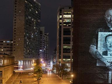 Tokoh TV Uruguay Diego Gonzalez memegang gambar Carlos Arevalo, yang menghilang selama kediktatoran militer (1973-1985), diproyeksikan di dinding gedung dalam rangka Peringatan March of Silence, saat pembatasan COVID-19, diadakan secara virtual di Montevideo, 20 Mei 2020. (Pablo PORCIUNCULA/AFP)