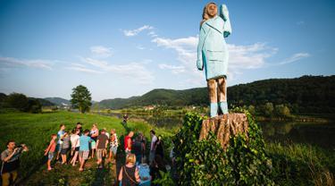 Orang-orang berkumpul dekat patung kayu yang menampilkan sosok Melania Trump di pinggiran Sevnica, Slovenia, 5 Juli 2019. Patung raksasa seukuran manusia itu  menampilkan sosok Melania yang mengenakan gaun biru yang dikenakan pada pelantikan suaminya tahun 2017. (Jure Makovec/AFP)