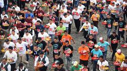 Pramusaji dari berbagai restoran berpartisipasi dalam Waiters Race ke-16 di Antigua, barat daya Ibu Kota Guatemala City, Rabu (14/11). Ratusan peserta beradu kecepatan sembari membawa nampan berisi dua minuman ringan, bir dan air. (JOHAN ORDONEZ/AFP)