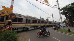 Sejumlah motor berhenti di pintu perlintasan kereta api Bintaro Permai yang tidak berfungsi di Jakarta, Kamis (25/10). Kondisi tersebut sangat membahayakan pengendara yang melintas. (Liputan6.com/Angga Yuniar)