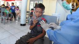 Petugas kesehatan menyuntikkan vaksin tetanus difteri ke siswa kelas 1 di SDI Al Hidayah, Cinere, Depok, Jumat (20/11/2020). Program imunisasi kepada pelajar di Kota Depok terus berjalan guna menjaga kesehatan anak dan meningkatkan imunitas tubuh di masa pandemi COVID-19. (merdeka.com/Arie Basuki)