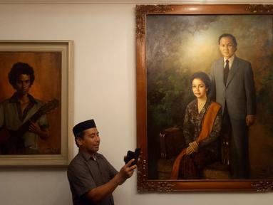 Pelayat memotret koleksi lukisan di rumah duka Presiden ke-3 RI BJ Habibie, Patra Kuningan, Jakarta, Rabu (11/9/2019). BJ Habibie meninggal pada Rabu, 11 September 2019 pukul 18.05 WIB. (Liputan6.com/Angga Yuniar)