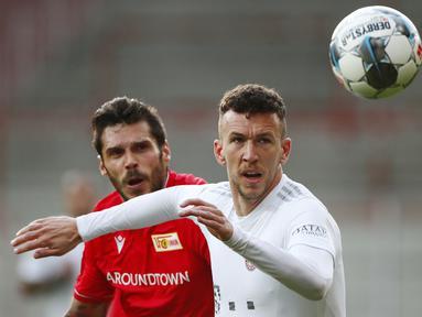 Gelandang Bayern Munchen, Ivan Perisic, berebut bola dengan pemain Union Berlin, Christopher Trimmel, pada laga Bundesliga  di Alte Foersterei, Minggu (17/5/2020). Bayern Munchen menang 2-0 atas Union Berlin. (AP/Hannibal Hanschke)