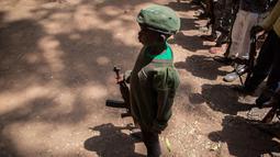 Tentara anak yang baru dibebaskan berdiri dengan senapan pada sebuah upacara di Yambio, Sudan Selatan, (7/2). Anak-anak ini secara resmi telah dilucuti senjatanya dan diberikan pakaian sipil. (AFP PHOTO/Stefanie Glinski)