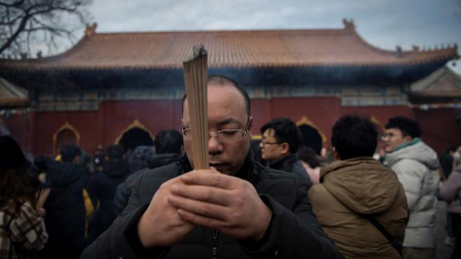 Seorang pria berdoa untuk keberuntungan pada hari kelima Tahun Baru Imlek di Yonghegong, atau Kuil Lama di Beijing (9/2). Warga China di seluruh dunia menyambut Tahun Babi pada 5 Februari.  (AFP Photo/Nicolas Asfouri)#source%3Dgooglier%2Ecom#https%3A%2F%2Fgooglier%2Ecom%2Fpage%2F%2F10000