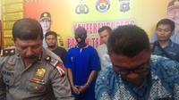 Penganiaya bocah berumur 11 tahun (baju biru) di Mapolsek Tenayanraya, Kota Pekanbaru. (Liputan6.com/M Syukur)