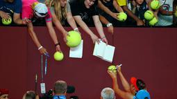 Petenis Rusia, Maria Sharapova memberi tanda tangan usai pertandingan melawan Caroline Wozniacki asal Denmark pada pertandingan babak ketiga Australia Open di Melbourne Park, Australia (18/1). Sharapova menang tiga set 6-4 4-6 6-3. (AFP Photo/David Gray)