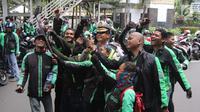 Sejumlah pengemudi ojek online berswafoto dengan polisi saat melakukan aksi di seberang Istana Merdeka, Jakarta, Selasa (27/3). (Liputan6.com/Arya Manggala)
