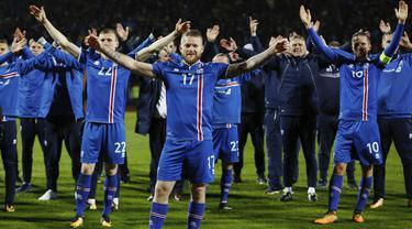 Kapten Islandia, Aron Gunnarsson, bersama rekan-rekannya merayakan keberhasilan lolos ke Piala Dunia 2018 usai mengalahkan Kosovo di Reykjavik, Senin (9/10/2017). Islandia untuk pertama kali dalam sejarah lolos ke Piala Dunia. (AP/Brynjar Gunnarsson)