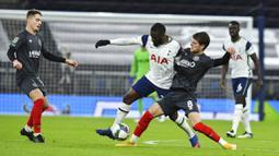 Pemain Tottenham Hotspur, Tanguy Ndombele, berusaha melewati pemain Brentford, Mathias Jensen, pada laga Piala Liga Inggris, di London, Rabu (06/01/2021). Spurs menang dengan skor 2-0. (Glyn Kirk/Pool via AP)