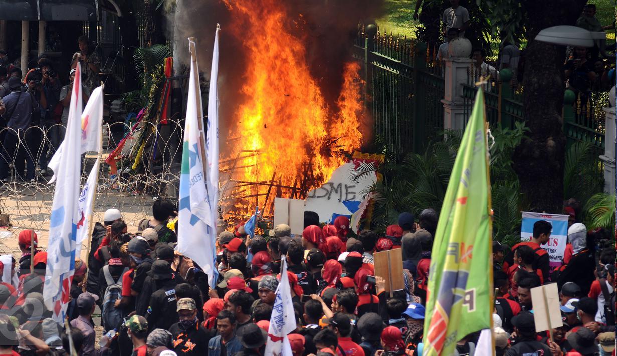 Sebuah karangan bunga dibakar massa saat aksi perayaan MayDay di Jalan Medan Merdeka Barat, Senin (5/1). Ribuan massa buruh turun ke jalan dalam perayaan Hari Buruh Internasional. (Liputan6.com/Helmi Fithriansyah)