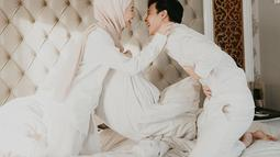 Potret Dinda Hauw dan Rey Mbayang berhasil bikin baper netizen. Keduanya selalu pamerkan keserasian di setiap gaya penampilan. Saat pemotretan dengan mengenakan baju putih, pasangan yang menikah 10 Juli 2020 terlihat mesra dengan saling bergurau di atas kasur. (Liputan6.com/IG/@dindahw)